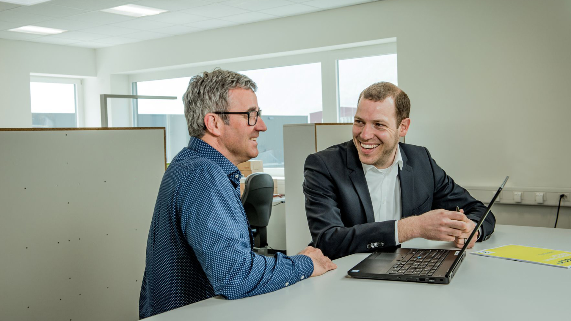 Two Bilfinger employees sit together at a desk with a laptop